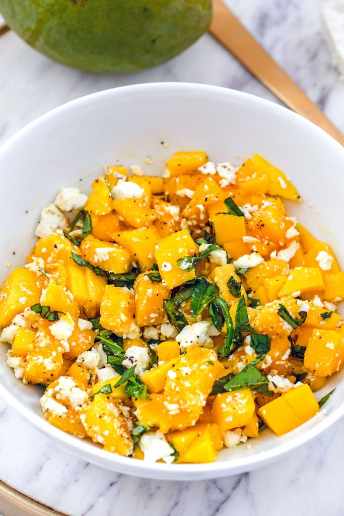 Head-on view of a white bowl with mango and feta salad with basil on a marble surface with mango and gold serving piece in the background