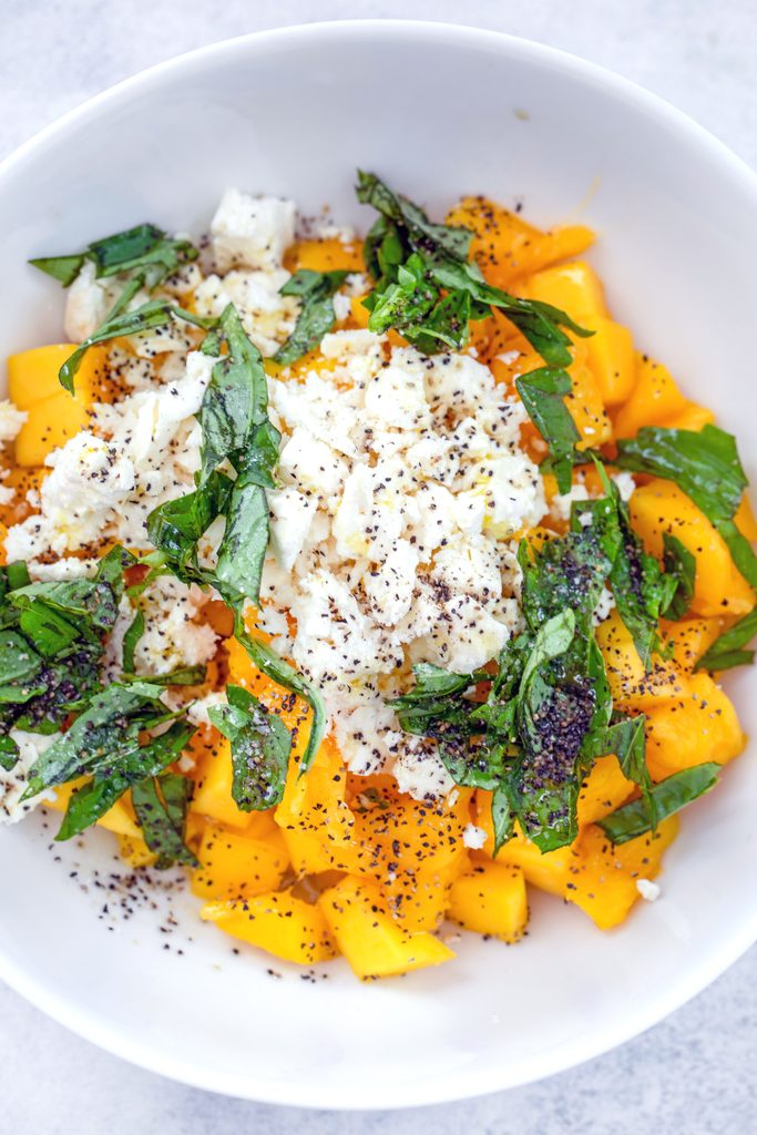 Overhead view of ingredients for mango and feta salad in a bowl, including chopped mango, sliced basil, feta, olive oil, and salt and pepper