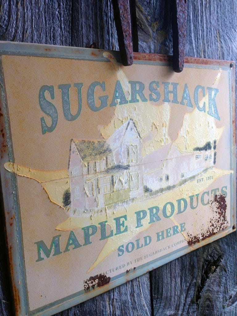 "Sign on the front of the sugar shack that says ""Sugarshack"" and ""Maple Products Sold Here"""