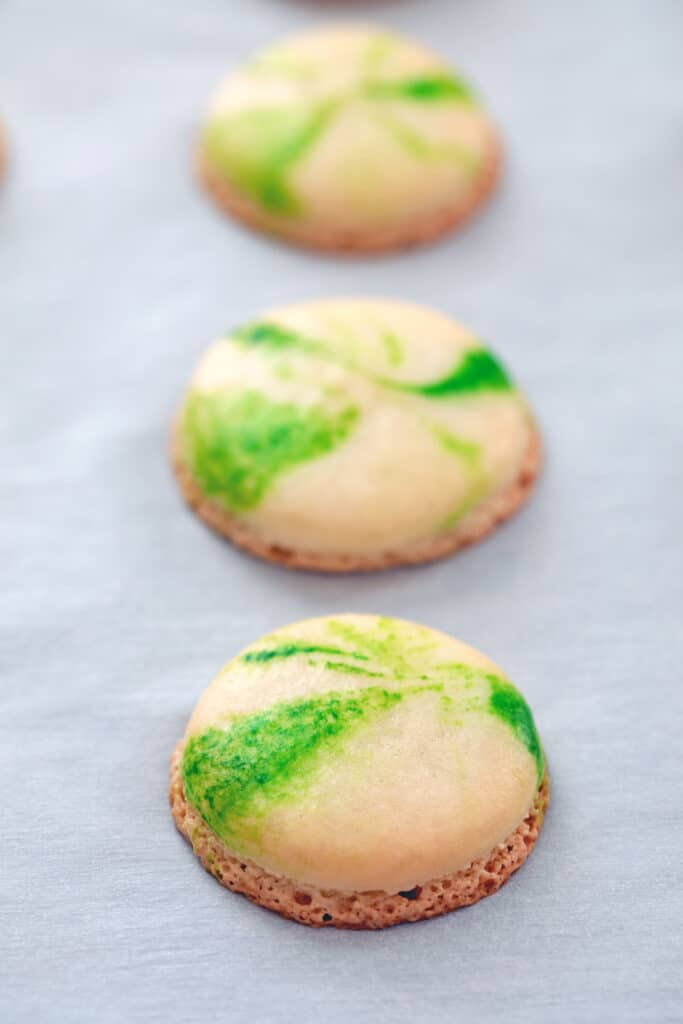 Head-on view of marbled green macarons just baked out of the oven