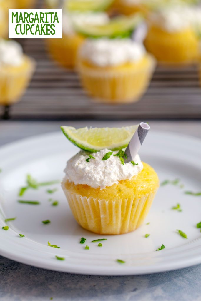 Head-on view of a mini margarita cupcake on a white plate with lime zest, lime wedge, and mini straw with more cupcakes in background and recipe title at top