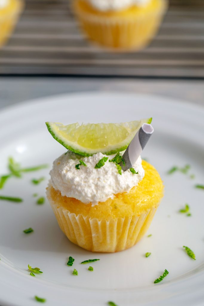 Closeup head-on view of a mini margarita cupcake topped with lime zest, a lime wedge, and a little straw on a white plate with more lime zest and a baking rack with more cupcakes in the background