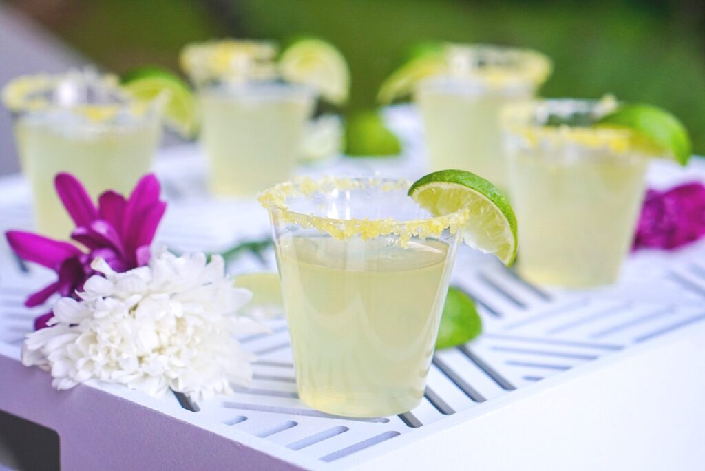 Margarita jello shots in little cups with salted rims and lime wedge garnish