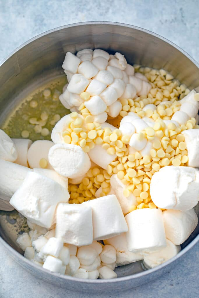 Overhead view of marshmallows and white chocolate chips in a saucepan with butter