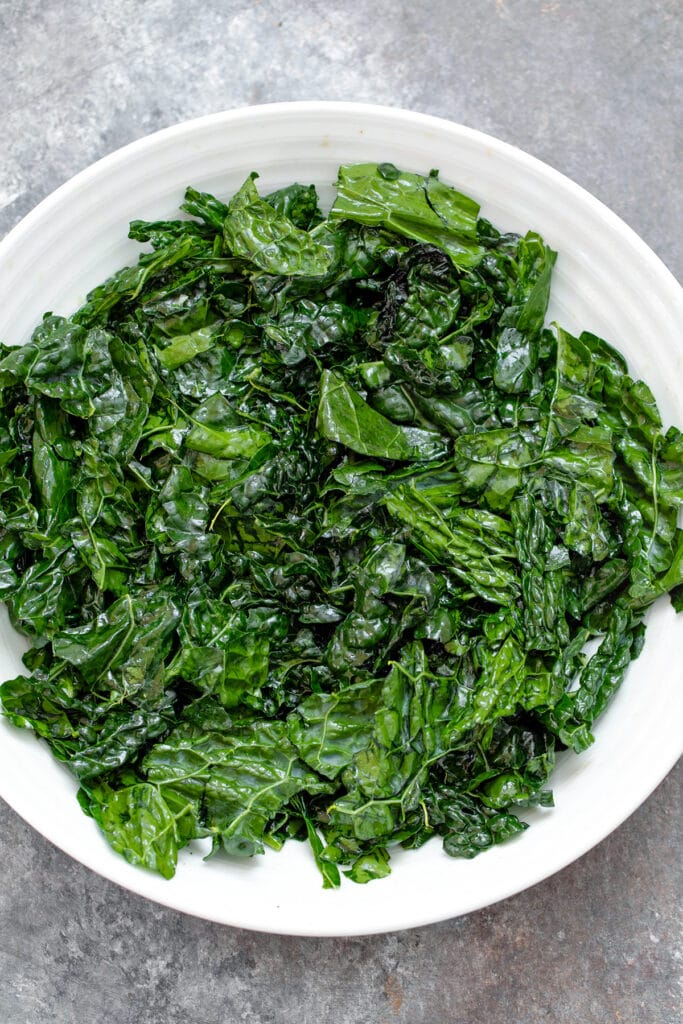 Overhead view of massaged kale in big white bowl