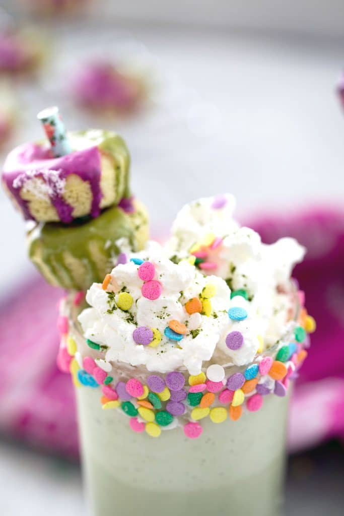 Overhead close-up view of matcha milkshake with whipped cream, sprinkles, and mini donuts on straw