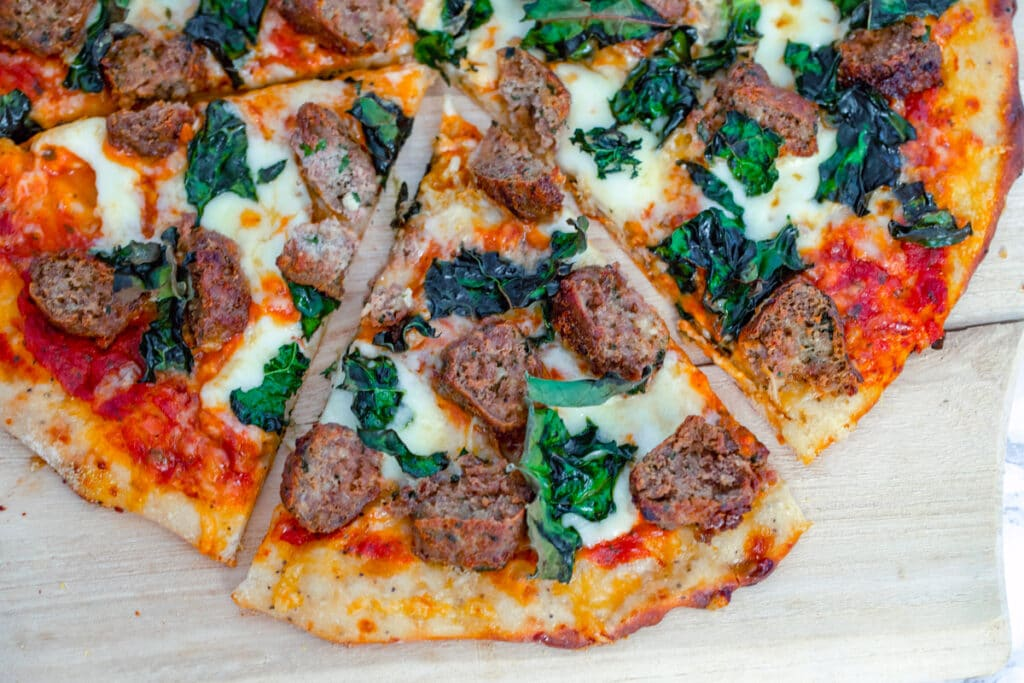 Landscape overhead view of meatball flatbread with kale, tomato sauce, and cheese, with one slice pulled out from rest of pizza