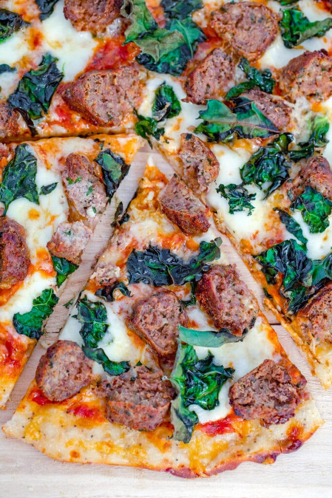 Overhead closeup view of slice of meatball flatbread pulled out from rest of pizza