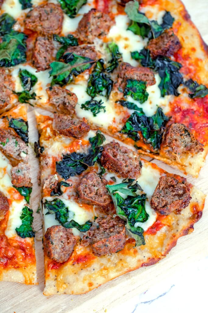Overhead view of a slice of meatball flatbread with cheese and kale pulled out from the rest of the pizza