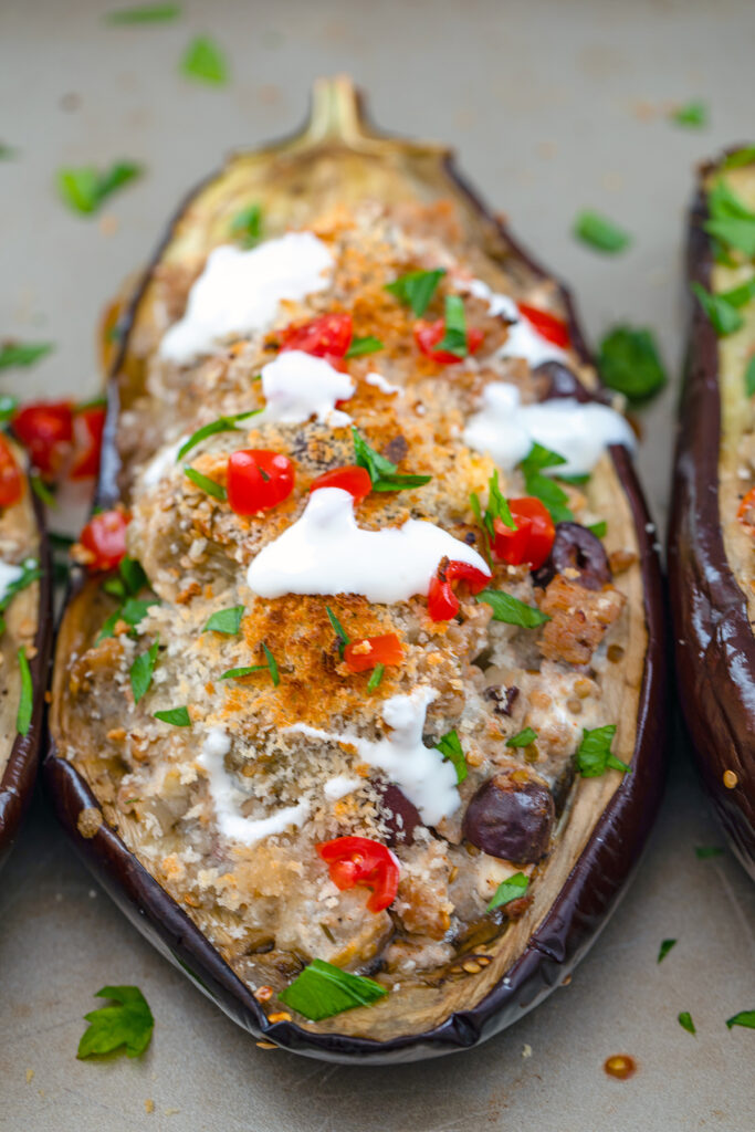 Overhead view of Mediterranean Turkey Stuffed Eggplant topped with tomatoes, olives, parsley, and sour cream