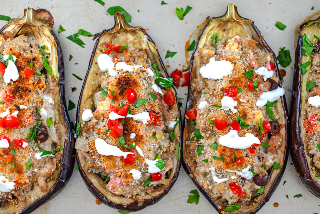 Overhead view of four eggplant halves stuffed with Mediterranean turkey mixture, baked, and topped with tomatoes, parsley, and sour cream