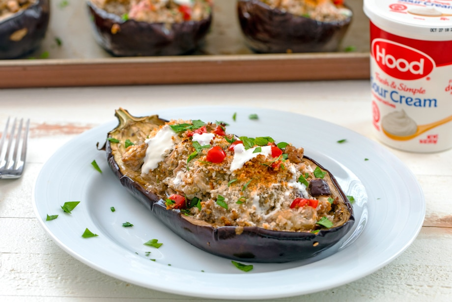 Landscape view of Mediterranean turkey stuffed eggplant half on a white plate with fork, container of Hood Sour Cream, and more eggplants on a baking sheet in the background