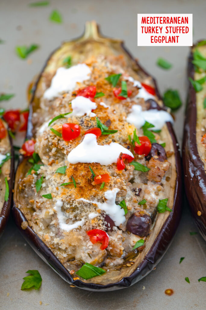 Overhead view of Mediterranean Turkey Stuffed Eggplant topped with tomatoes, olives, parsley, and sour cream with recipe title at top of image