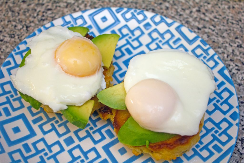 Overhead view of biscuits on a plate topped with avocado and poached eggs