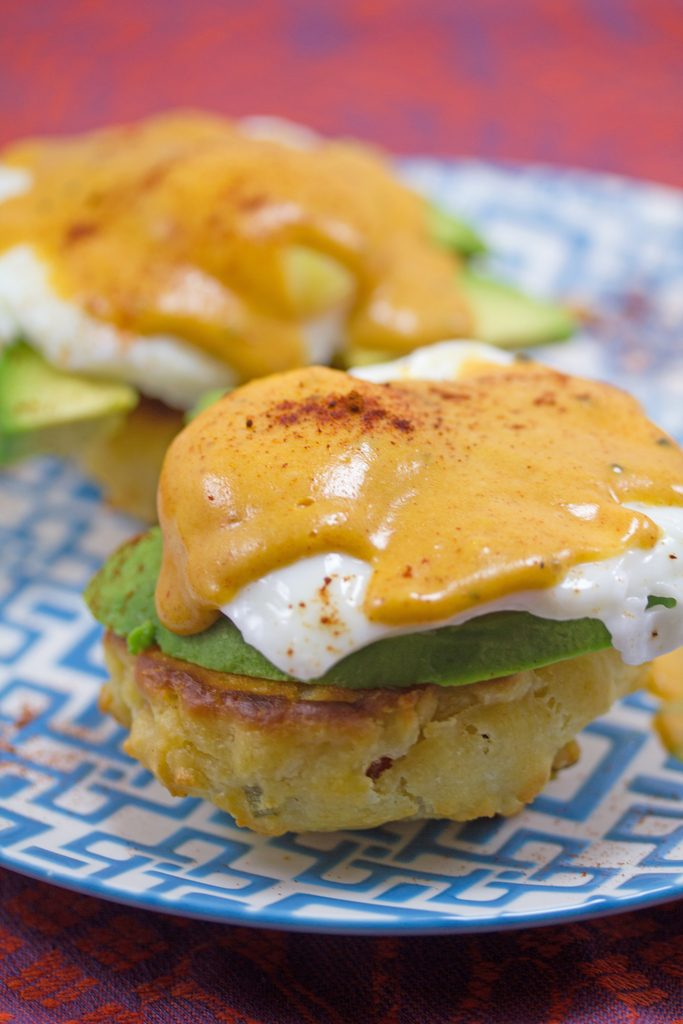 Head-on closeup view of a chorizo biscuit topped with avocado, poached egg, and chipotle hollandaise for Mexican eggs Benedict