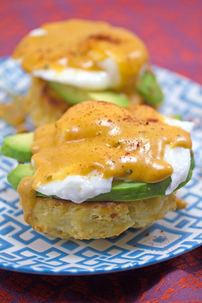 Head-on view of Mexican eggs Benedict on a blue and white plate with chorizo biscuits, avocado, poached eggs, and chipotle hollandaise sauce