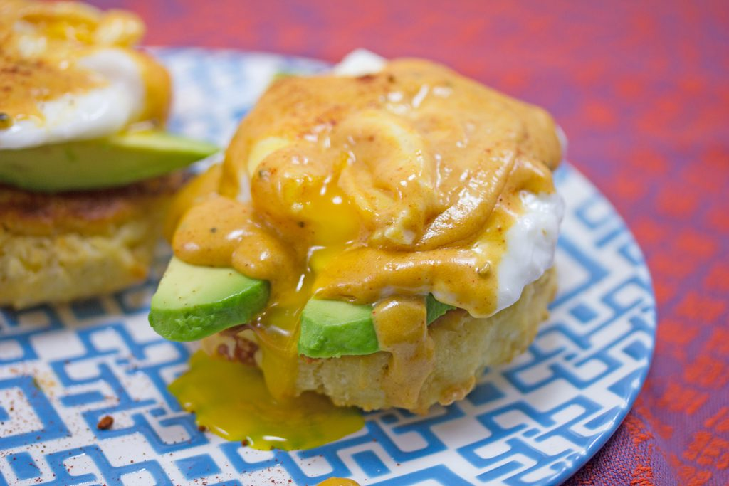 Landscape overhead view of Mexican eggs Benedict on a blue and white plate with yolk broken and drizzling onto plate