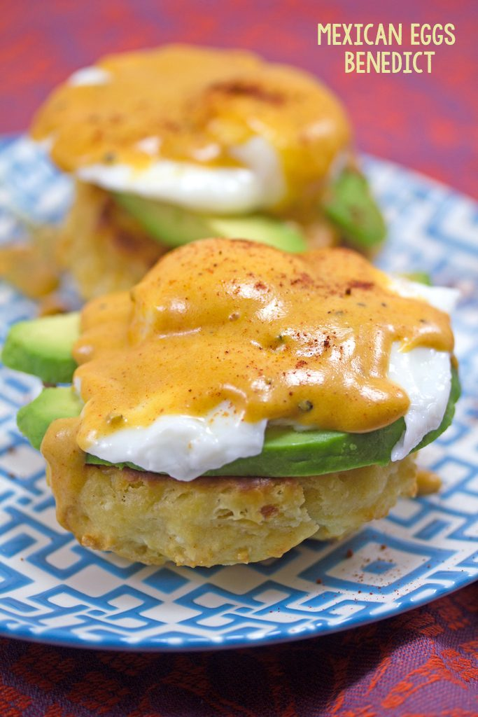 Head-on view of Mexican eggs Benedict on a blue and white plate with chorizo biscuits, avocado, poached eggs, and chipotle hollandaise sauce with recipe title at top