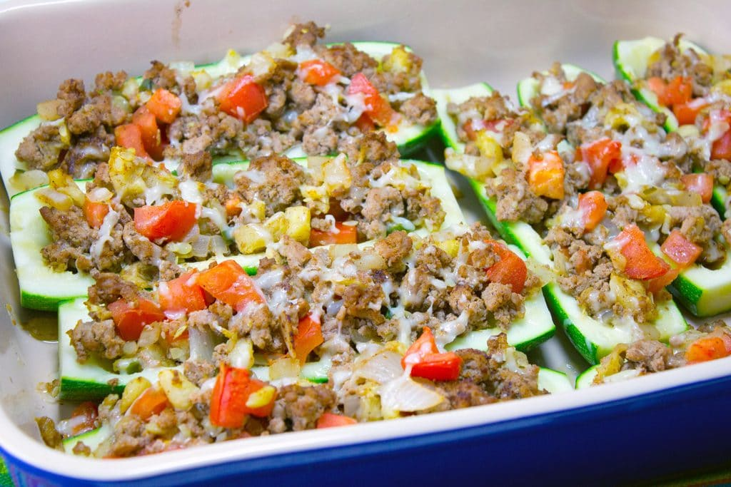 Landscape view of 8 Mexican zucchini boats with turkey and tomatoes in a blue casserole dish