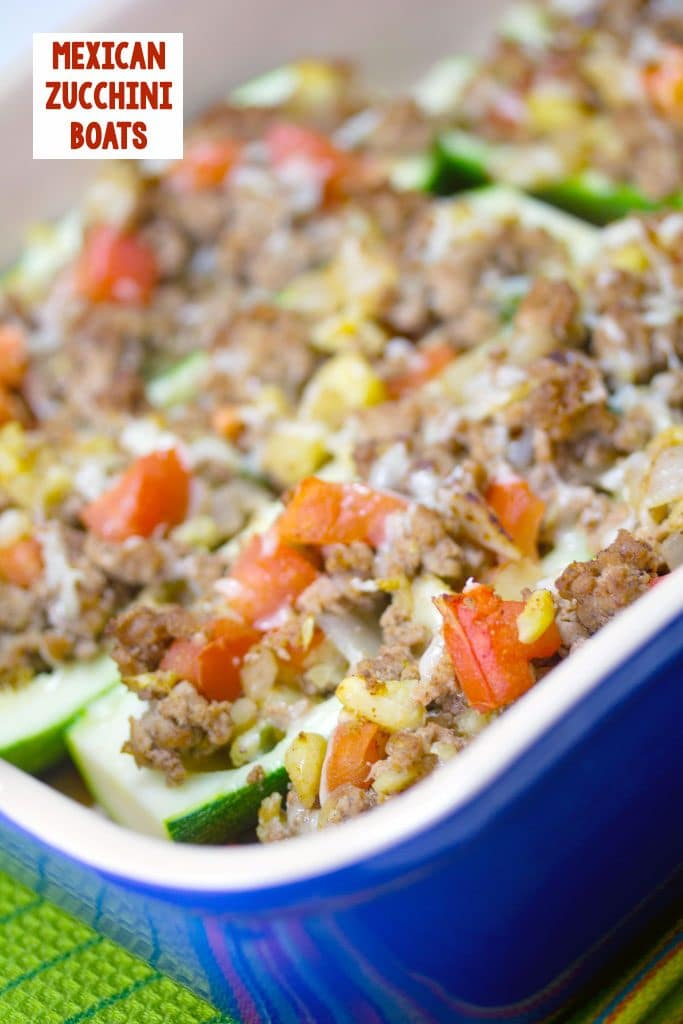 Sideways view of Mexican zucchini boats with turkey and tomatoes  in a blue casserole dish with recipe title at the top of the image