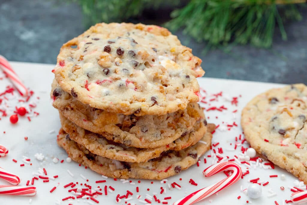 Landscape view of multiple Milk Bar Cornflake Chocolate Chip Candy Cane Cookies with red and white sprinkles and candy canes