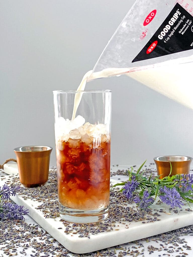 Milk being poured into ice-filled glass with coffee