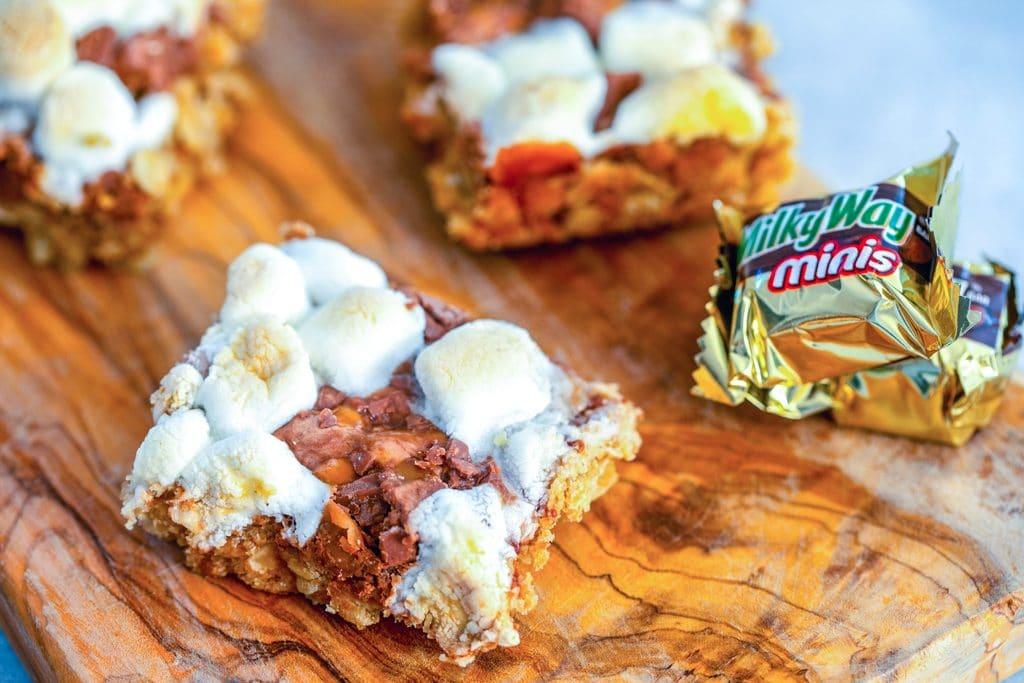 Landscape view of Milky Way s'mores granola bar squares on a wooden board with wrapped Milky Way minis in background