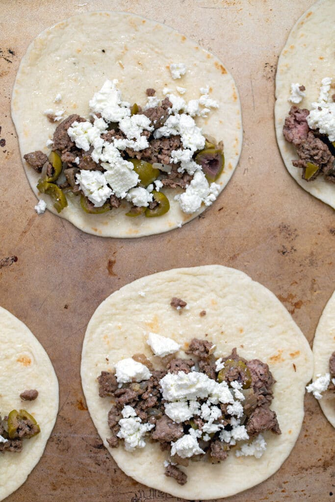 Flour tortillas on baking sheet topped with lamb filling and cheese