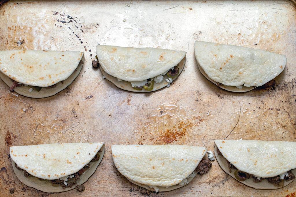 Mini tacos folded over on baking sheet