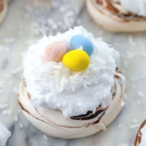 mini chocolate swirled pavlova topped with whipped cream with shredded coconut and mini Cadbury Eggs
