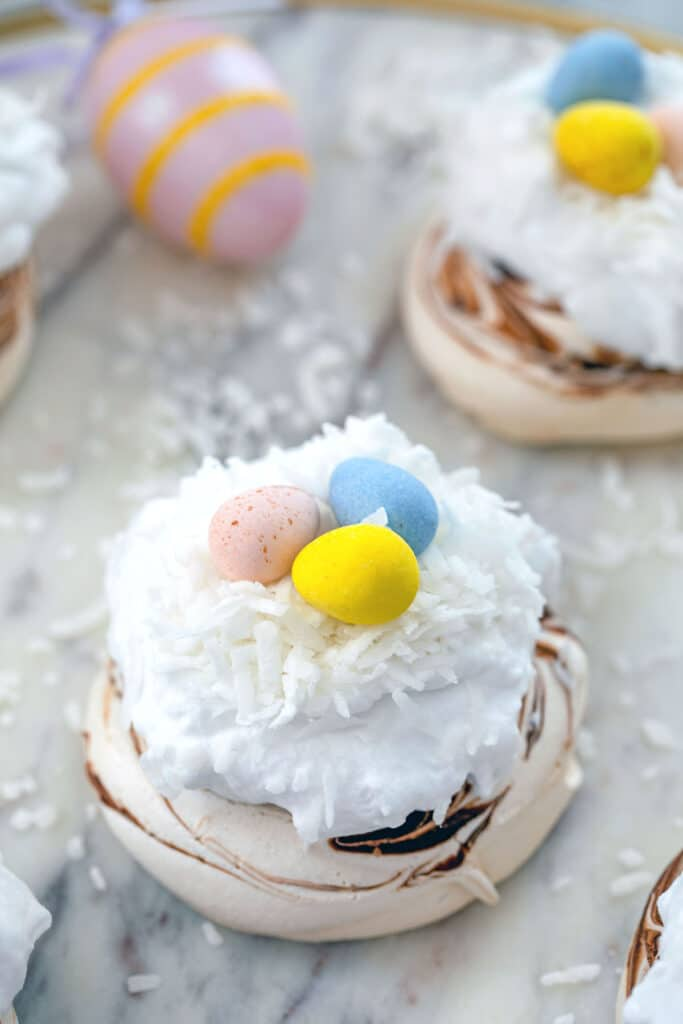 Head-on closeup of a chocolate swirled mini Easter pavlova topped with whipped coconut cream, shredded coconut, and Cadbury Mini Eggs on marble surface with Easter eggs and more pavlova in background