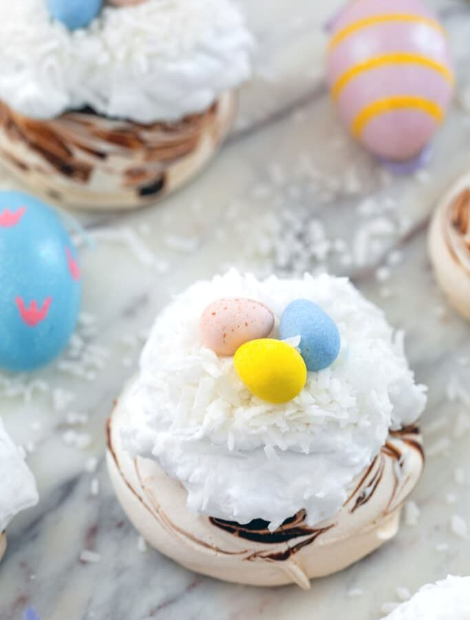 Mini Easter Pavlovas -- These Mini Easter Pavlovas have a chocolate swirled pavlova base and are topped with coconut whipped cream, shredded coconut, and Cadbury Mini Eggs. They make for a fun and delicious Easter dessert, but the mini pavlova base can be made any time of year | wearenotmartha.com