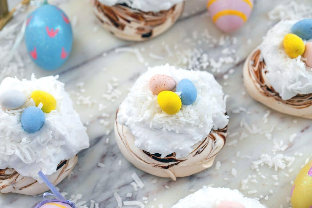 Landscape overhead view of multiple chocolate swirled mini Easter pavlovas topped with coconut whipped cream, shredded coconut, and Cadbury Mini Eggs on a marble surface surrounded by painted Easter eggs