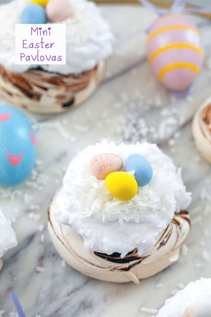 Head-on view of chocolate swirled mini Easter pavlovas topped with whipped cream, coconut, and Cadbury Mini Eggs on a marble surface with Easter eggs in background and recipe title at top