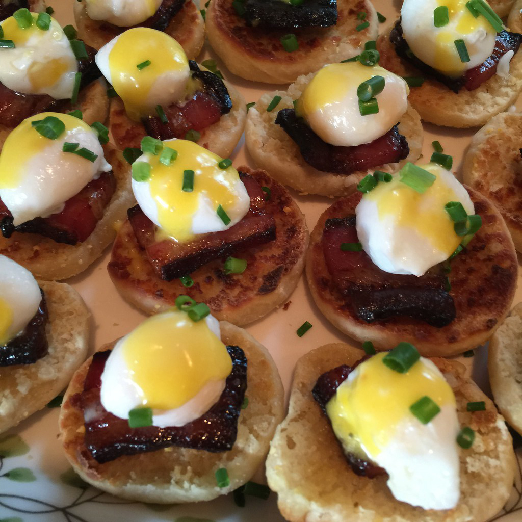 Overhead view of mini eggs benedict with homemade bacon, hollandaise sauce, and chives
