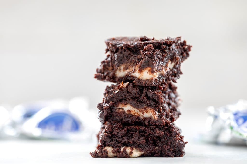 Landscape head-on photo of three mint chocolate brownies stacked on each other with peppermint patty wrappers in the background