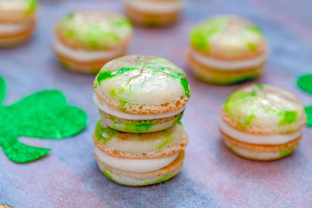 Head-on landscape view of a stack of mint macarons with Baileys buttercream with more macarons scattered around and glittery shamrocks