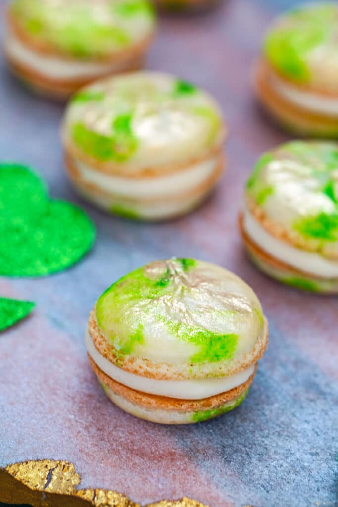 Head-on view of mint macarons with Baileys buttercream on a pink marbled board with sparkly green shamrocks