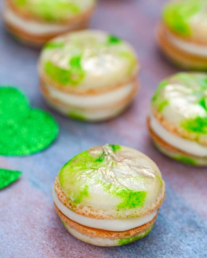 Mint macarons with Baileys buttercream set on a pink and gold platter with green glitter shamrock and more macarons in background