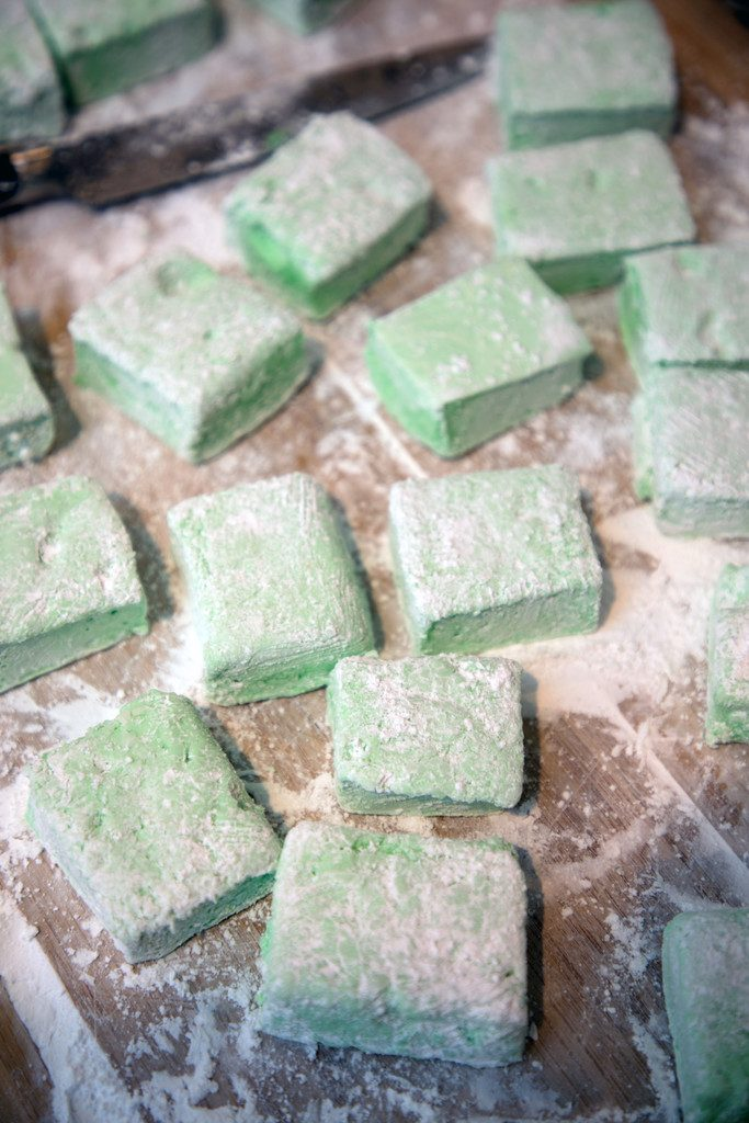 Overhead view of just cut green mint marshmallows sitting in powdered sugar on cutting board