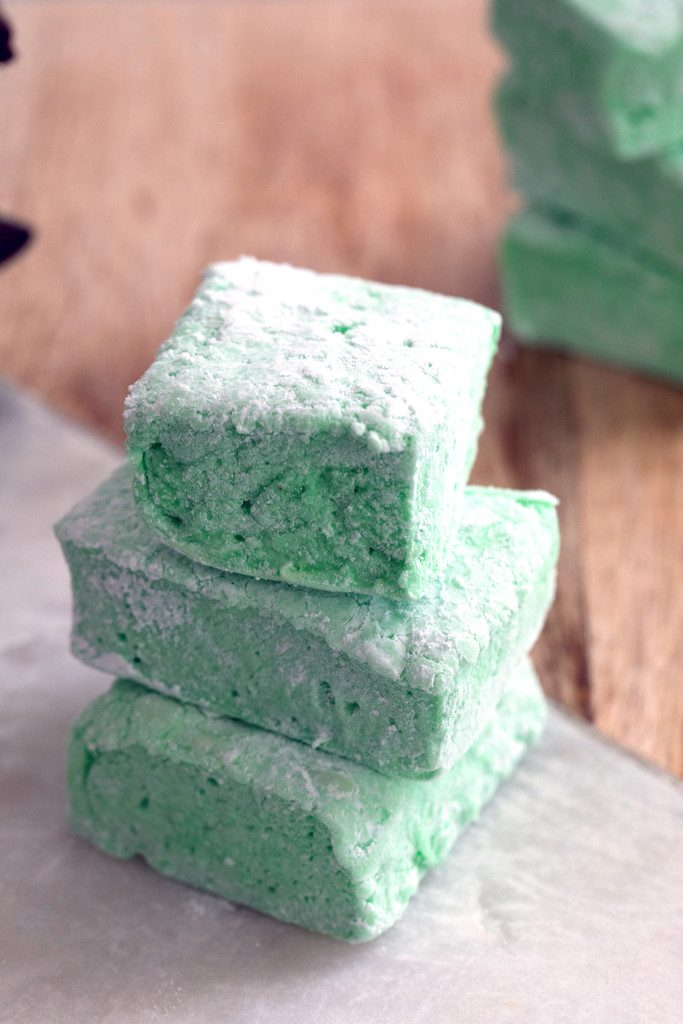 Head on view of three homemade green mint marshmallows stacked on top of each other on wood cutting board