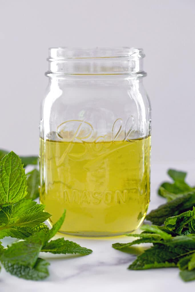 Head-on view of greenish colored mint simple syrup in a mason jar with mint leaves all around