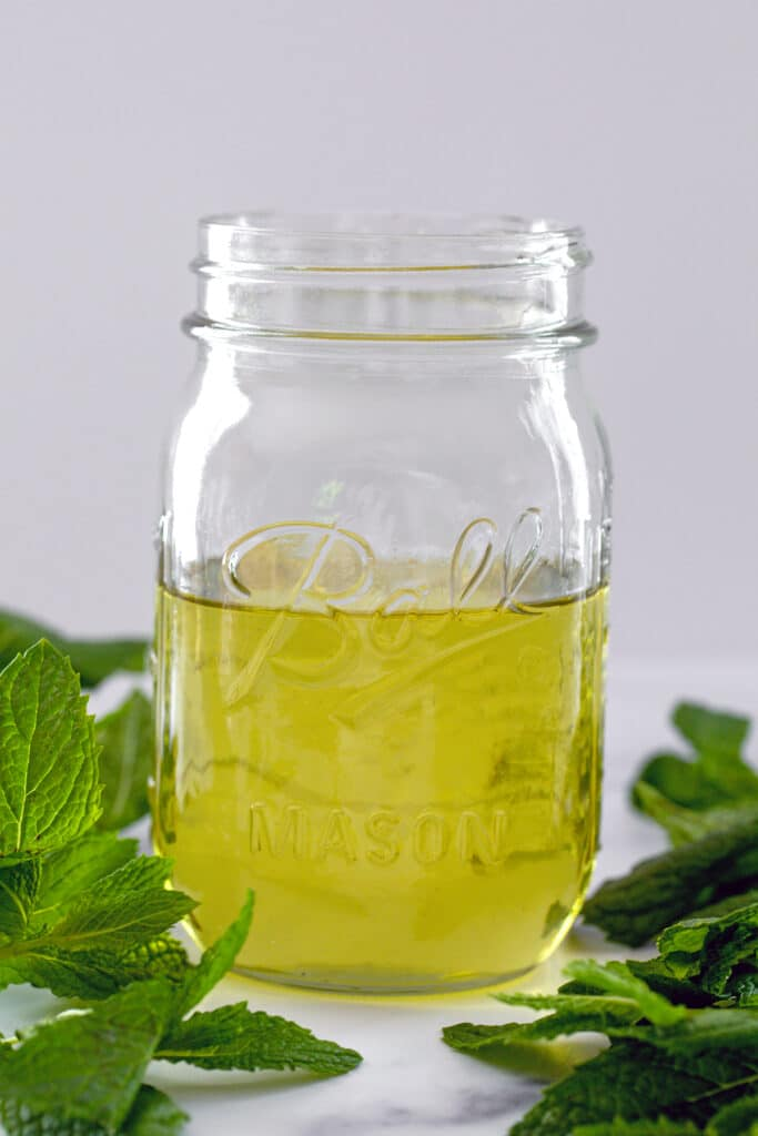 Head-on closeup view of a mason jar filled halfway with greenish colored mint simple syrup with fresh mint leaves all around