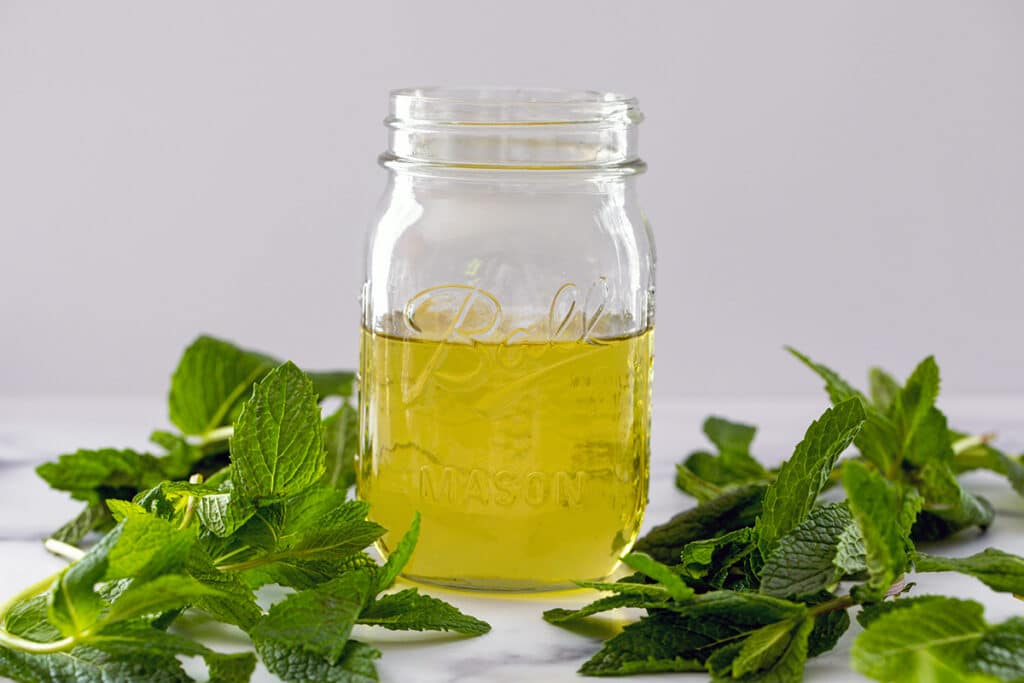 Landscape head-on view of a mason jar of mint simple syrup with fresh mint leaves all around