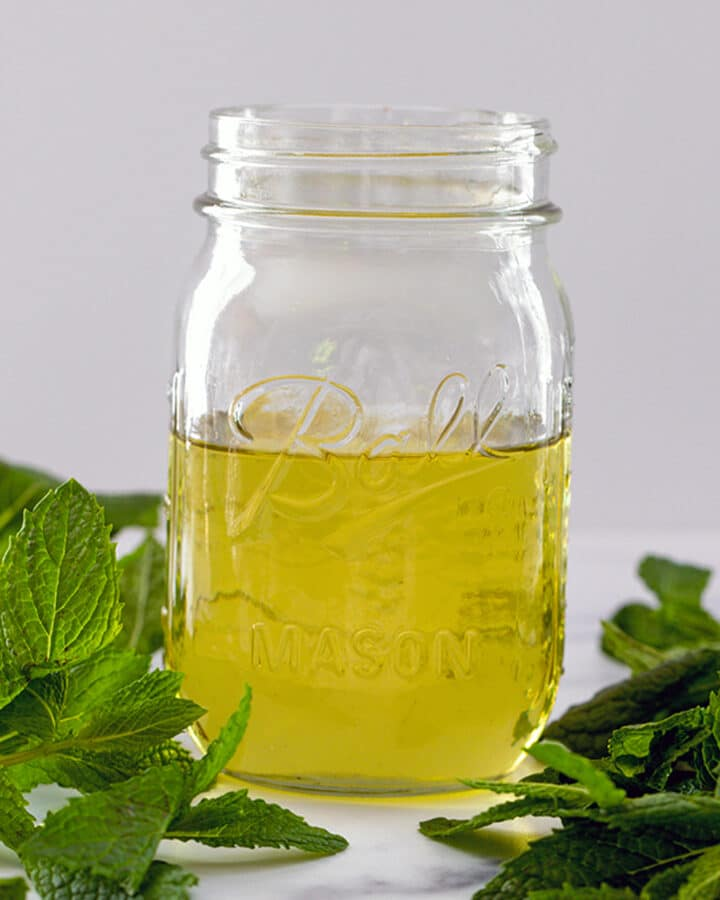Head-on view of a mason jar of mint simple syrup with mint leaves all around