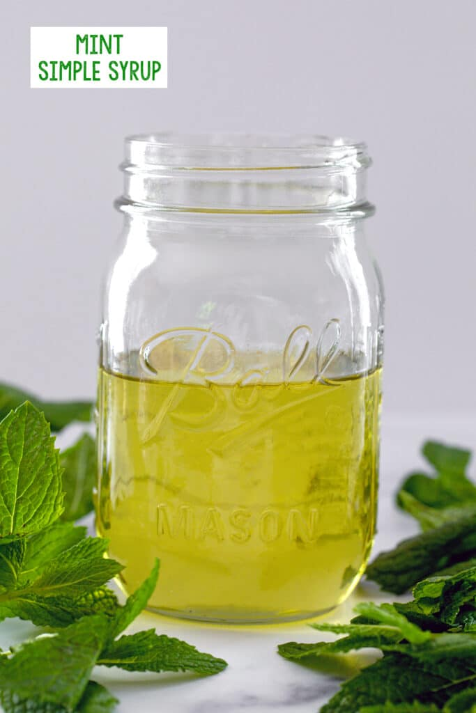 Head-on closeup view of a mason jar filled halfway with greenish colored mint simple syrup with fresh mint leaves all around and recipe title at top