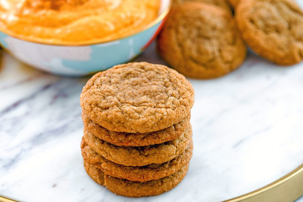 Landscape head-on view of a stack of molasses ginger cookies on a marble tray with bowl of sweet pumpkin dip and more cookies in the background