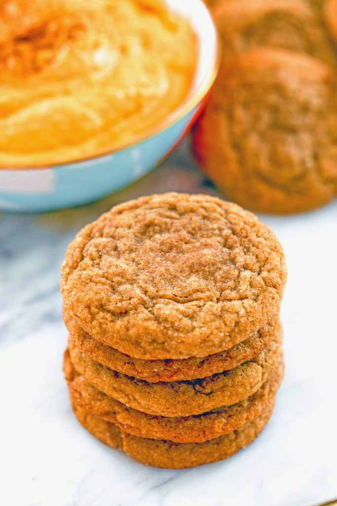 Head-on view of a stack of molasses ginger cookies on a marble surface with bowl of sweet pumpkin dip and more cookies in the background