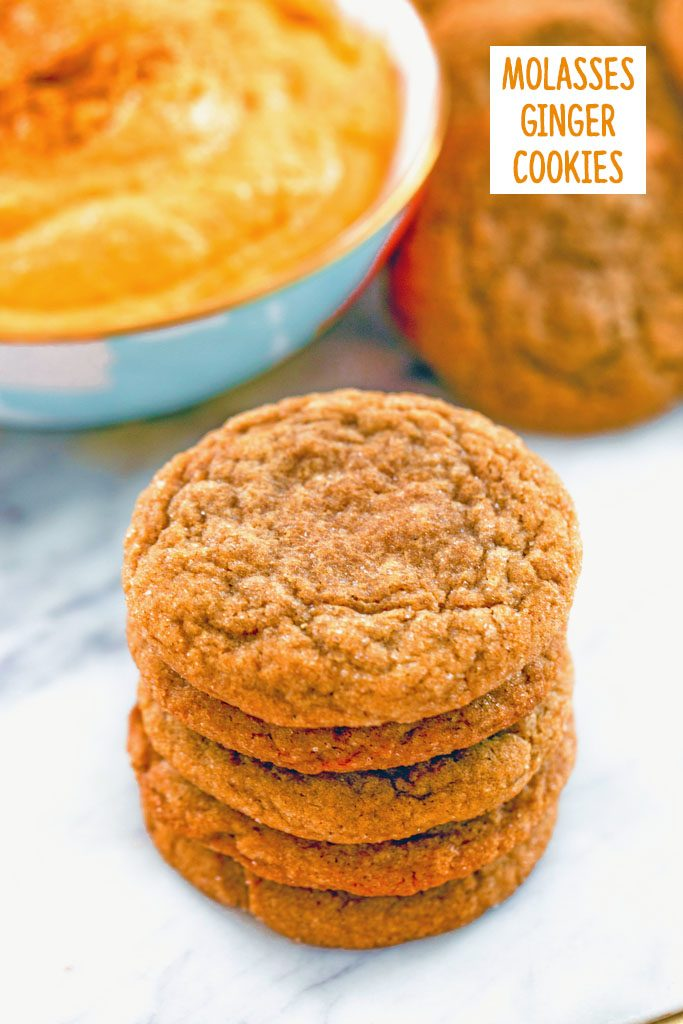 Head-on view of a stack of molasses ginger cookies on a marble surface with bowl of sweet pumpkin dip and more cookies in the background and recipe title at top