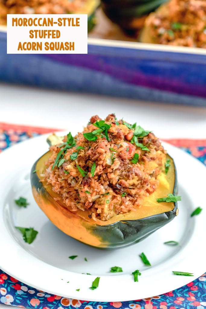 Head-on view of a half an acorn squash stuffed with a beef and bulgur mixture on a white plate with a casserole dish with more squash in the background and recipe title at top